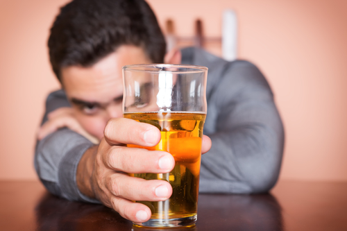 Drunk hispanic man holding a glass of beer
